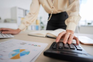 Business lady calculating revenue for financial report, selective focus