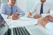 részleges kilátás nyílik üzletemberek asztalnál papírok és laptop