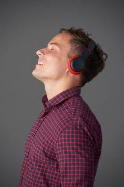 Smiling young man in headphones enjoying his favorite music