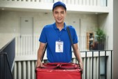 Photo Young Asian delivery man with big bag of pizza