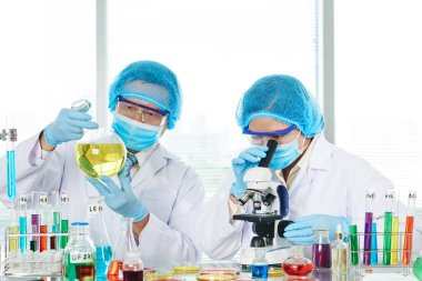 Scientist doctors working in laboratory and using microscope stock vector