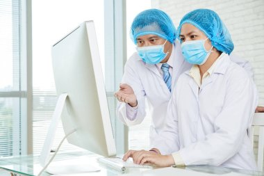 Doctors wearing medical masks and white coats studying statistic data on computer monitor in laboratory stock vector