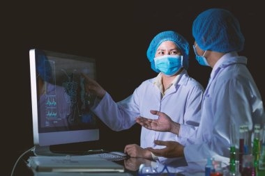 Researchers wearing medical masks and white coats studying statistic data on computer monitor in laboratory stock vector