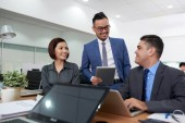 Veselá bílý límeček pracovníků v kanceláři u stolu s notebooky