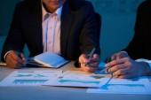 Közelkép kép munkatársai pénzügyi grafikonok üzleti találkozó megbeszélése