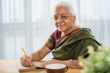 Cheerful elderly Indian woman in sari writing in diary at table stock vector