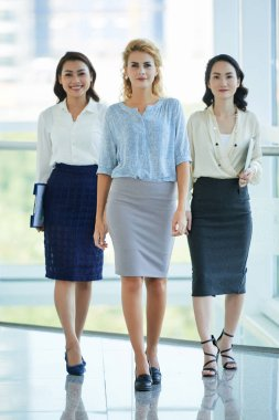 Confident beautiful businesswomen in skirts approaching to camera
