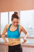 Šťastné mladé fit žena měření pasu po tréninku