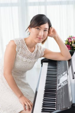 Portrait of pretty talented Korean woman leaning on piano