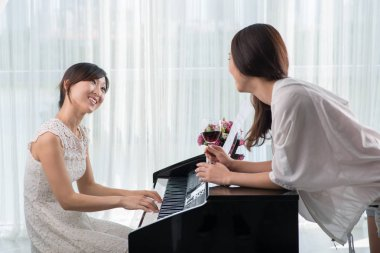 young asian woman with red wine glass listening to music of friend playing piano