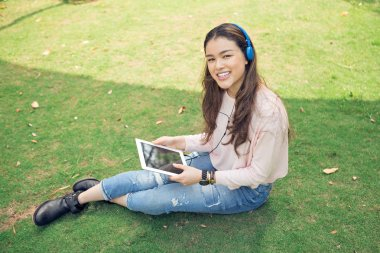 Pretty Vietnamese college girl sitting on campus with tablet computer