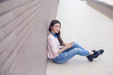Teenage girl sitting on ground and listening to music in smartphone