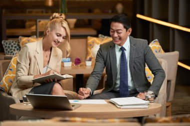 Cheerful international business team working with papers at meeting