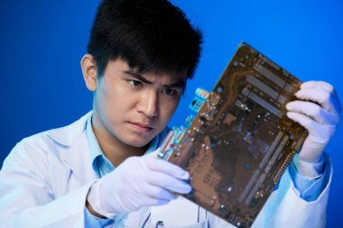 Professional Asian electronic engineer looking at big circuit board in his hands