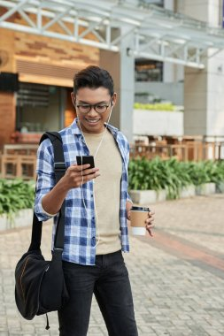 smiling Asian man in headphones browsing smartphone and holding coffee mug