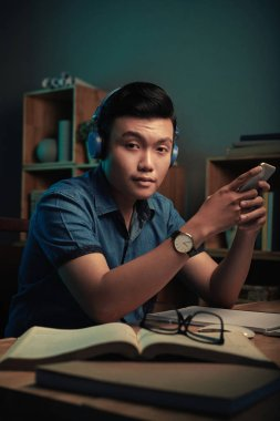 Handsome Asian man with smartphone sitting at his table at home