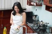 Fotografie Charmante Asiatin in weißer Schürze beim Abwasch mit Schwamm stehen in modernen Küche