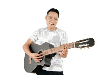 Portrait of young handsome Asian male musician playing the guitar and smiling at camera happily against white background