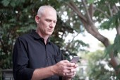 Low angle view of attractive mature Caucasian man texting on smartphone while standing in park on blurred background