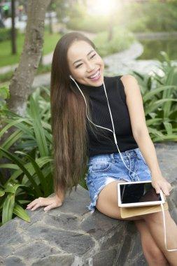 Beautiful laughing Vietnamese woman in earphones watching videos on tablet computer