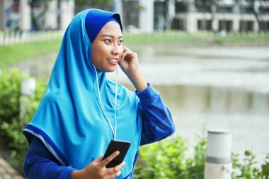 Beautiful Indonesian woman in hijab smiling and listening to music in earphones and holding mobile
