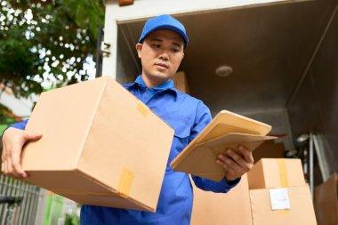 Courier reading address on tablet computer before delivering parcel