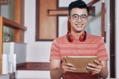 Portrait of happy young Vietnamese man with digital tablet and headphones