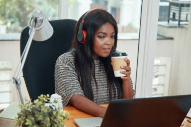 Pretty young Black woman in headset drinking coffee and working on laptop in office