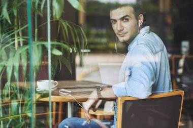 Attractive young man sitting at cafe table and turning to camera