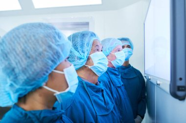 Side view of four surgeons in masks standing in modern operating theater and looking at display together