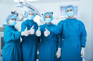 Asian surgical team in masks and uniform looking at camera and showing thumb-up gesture while standing in operating theater together