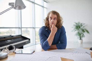 Portrait of pensive creative musician writing new song