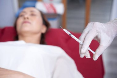 Gloved hand of beautician holding syringe with hylaruonic acid