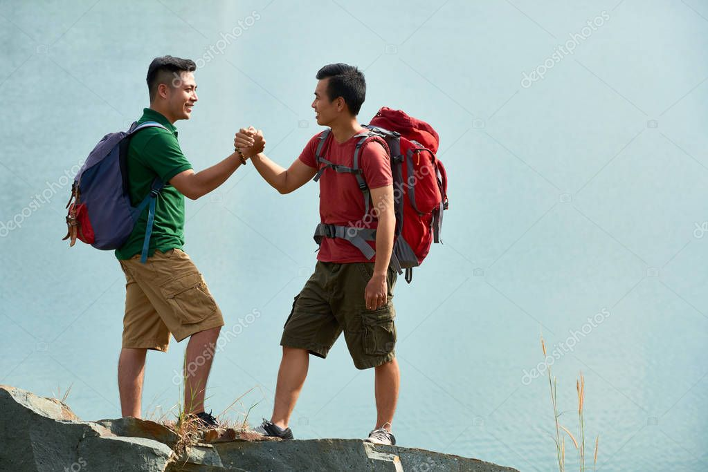 Cheerful Vietnamese hikers shaking hands after getting on top of mountain