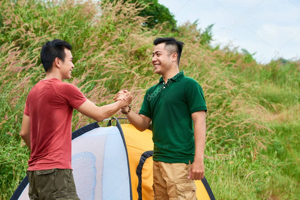 Happy friends shaking hands after setting up tent on camping site