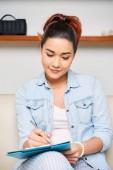 junge Frau sitzt auf Sofa mit Klemmbrett und füllt das Arbeitsformular aus