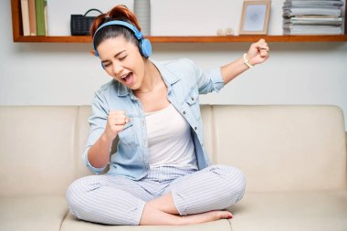 Young pretty girl in casual clothing sitting on couch in headphones and singing