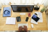 Přehled počítačového monitoru, miniaplikace, papíry a další potřeby na dřevěný stůl kde programátor pracuje