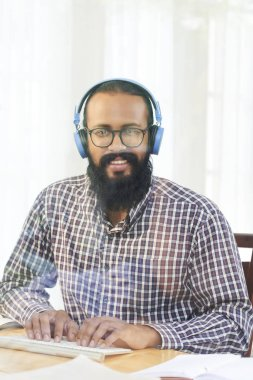 Bearded professional in casual shirt, headphones and eyeglasses looking at you while typing on keypad by desk