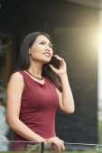 Beautiful Asian  businesswoman standing outdoors and smiling during a conversation on the phone