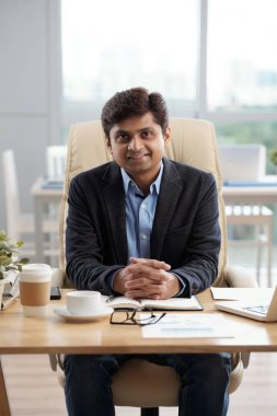 Confident smiling CEO of company sitting at his office table