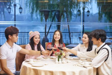 Cheerful young Asians people toasting with wine at dinner table