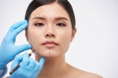 Fotografie Cosmetic surgeon drawing lines on face of young beautiful woman