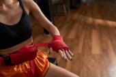 Weibliche Muay Thai Kämpfer, die Hände mit der roten Binde umwickeln