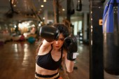 Photo Serious young Asian woman boxing in gym