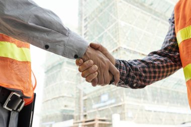 Foreman and construction engineer shaking hands before starting work on difficult project stock vector