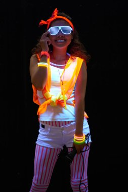 Cheerful young woman with microphone standing in darkness in glowing clothes