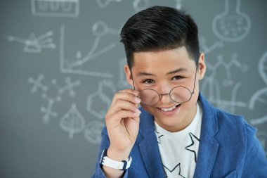 Portrait of smart Vietnamese teen boy adjusting glasses and looking at camera