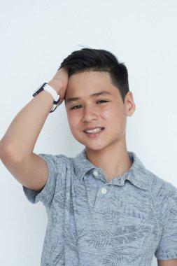 Smiling Asian teen boy tousling his hair and looking at camera