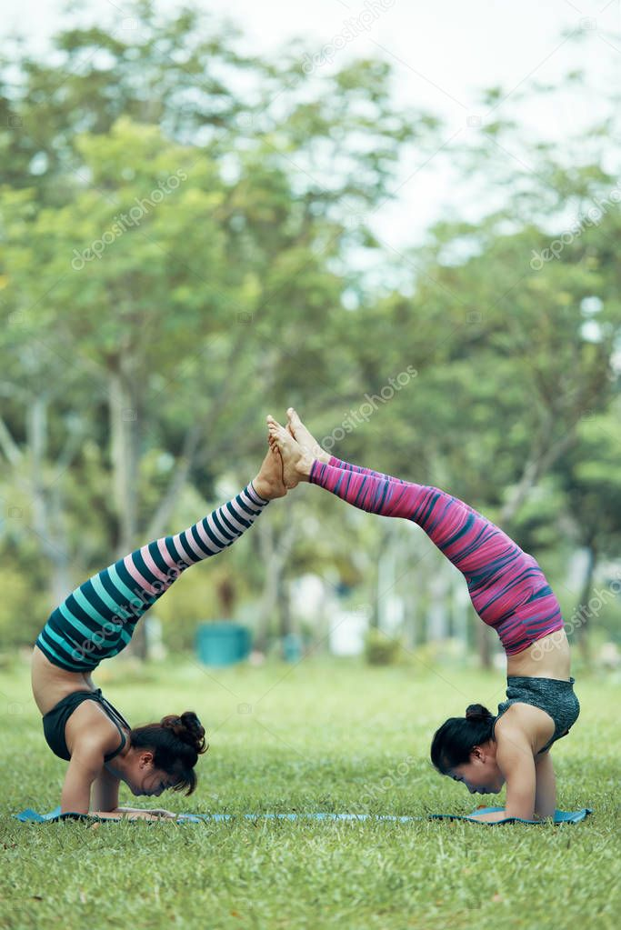 Vietnamese young women doing acroyoga in city park